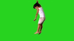 Happy little boy jumping and spinning on green scr Stock Video Footage