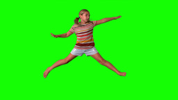 Girl jumping with limbs outstretched on green scre Stock Video Footage