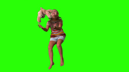 Girl jumping and catching teddy on green screen Footage