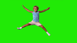 Boy jumping with limbs outstretched on green scree Footage