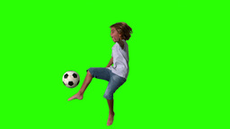 Boy jumping and kicking football on green screen Footage