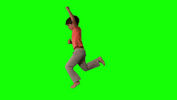 Side view of boy jumping up on green screen Footage