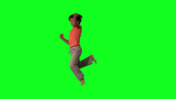 Side view of boy jumping up and down on green scre Stock Video Footage