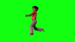 Side view of happy boy jumping up and down on green screen Footage