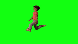 Side view of happy boy jumping up and down on gree Stock Video Footage