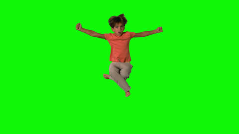 Boy jumping and cheering on green screen Footage