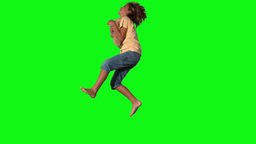 Boy jumping to catch teddy bear on green screen Stock Video Footage
