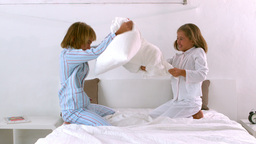 Siblings having a pillow fight on the bed Footage