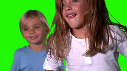 Cute siblings jumping together on green screen Footage