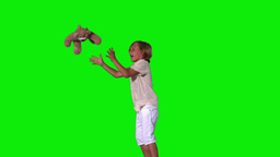 Cute boy jumping and catching teddy on green backg Stock Video Footage