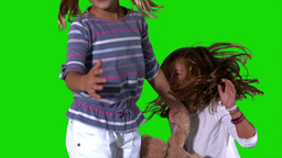 Sisters jumping on green screen with teddy Footage