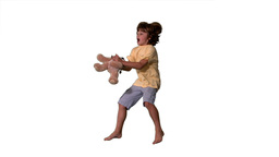 Young boy jumping up and catching teddy bear on wh Footage