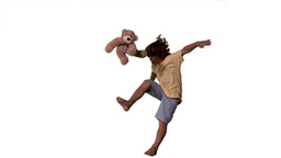Little boy jumping up and kicking teddy on white background Stock Video Footage