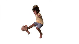 Little boy jumping up and kicking teddy on a white background Footage