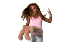 Little girl jumping up and turning with teddy on w Stock Video Footage