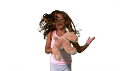 Little girl jumping up and turning with teddy on w Footage