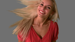 Attractive blonde tossing hair on grey background Footage