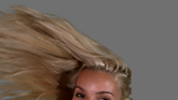 Attractive blonde tossing her hair up on grey back Footage