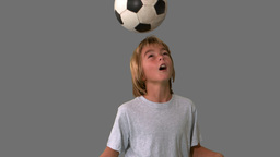 Young boy heading and kicking a football on grey b Footage
