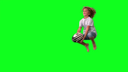 Boy jumping to catch rugby ball on green screen Footage