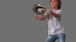 Boy jumping up to catch rugby ball on grey backgro Stock Video Footage