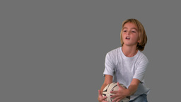 Boy catching rugby ball on grey background Footage
