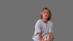 Boy catching rugby ball on grey background Stock Video Footage