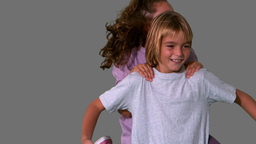 Sister jumping on brothers back on grey background Stock Video Footage