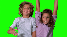 Brother and sister jumping up on green screen Footage