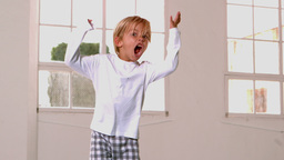 Boy in pajamas jumping and shouting in front of wi Footage