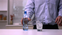 Man pouring water into a glass Stock Video Footage