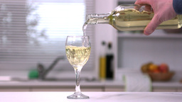 Mans hand pouring white wine from a bottle into a  Footage