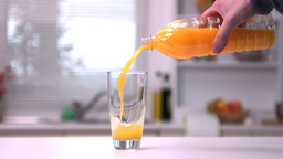 Mans hand pouring orange juice from a bottle into  Footage