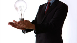 Man tossing an oversize light bulb Stock Video Footage