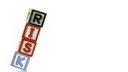 Blocks spelling Risk falling over on white backgro Stock Video Footage