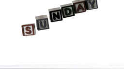 Sunday spelled out in letter blocks falling over Footage