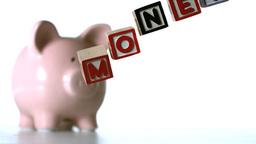 Alphabet blocks spelling money dropping down Footage