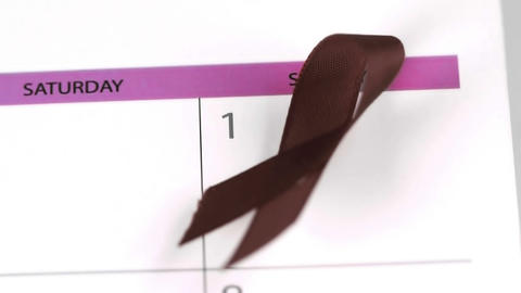 Red ribbon symbol for Aids falling on a calendar Footage