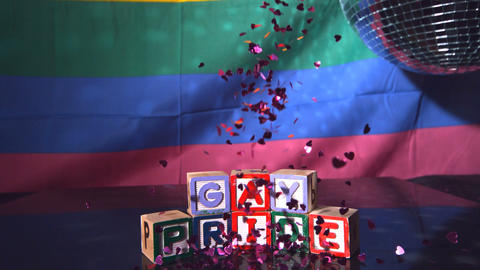 Heart confetti falling on blocks spelling gay prid Footage
