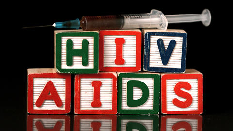 Syringe falling on blocks spelling Aids and Hiv Footage