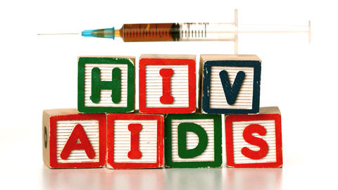 Needle falling on blocks spelling AIDS and HIV Footage