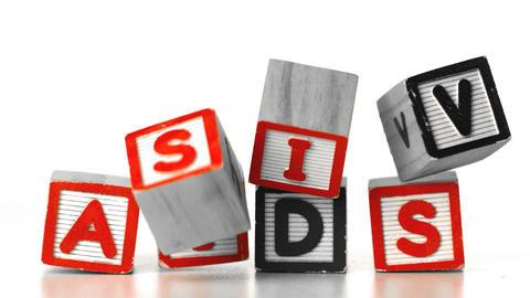Blocks spelling HIV falling on blocks spelling AID Stock Video Footage