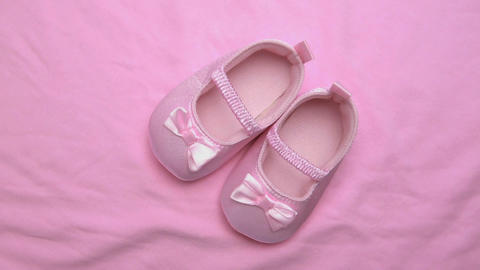 Pink baby booties on pink blanket Stock Video Footage