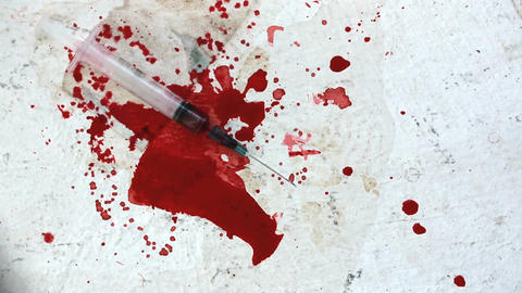 Syringes falling on bloody surface Stock Video Footage