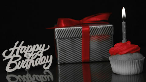 Candle on cupcake blown beside gift and happy birthday sign Stock Video Footage