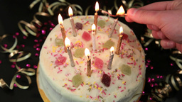 Hand lighting candles on birthday cake Footage