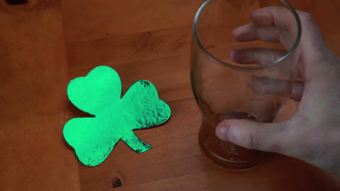 Hand putting down empty pint beside large shamrock Stock Video Footage