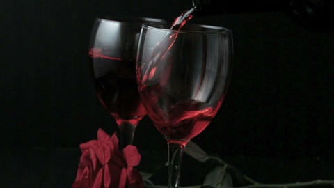 Two glasses of red wine being poured with red rose Footage