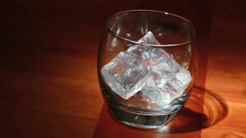 Tumbler of ice being filled with whiskey Stock Video Footage