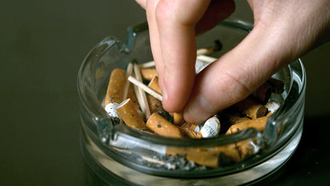 Hand Putting Cigarette Out In Ashtray stock footage